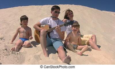 gezin, met, gitaar, en, mondharmonica, het zingen, op, strand