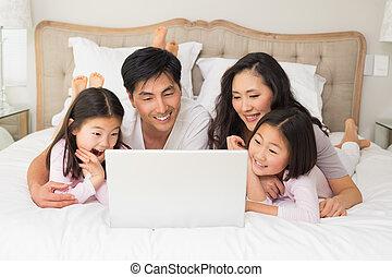 gezin, ontspannen, bed, vier, gebruikende laptop