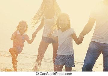 gezin, runing, ondergaande zon , plezier, strand, hebben
