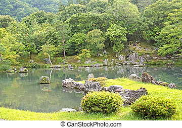 Ggreen plants, mountain, fish, lake with reflection in Japan zen garden