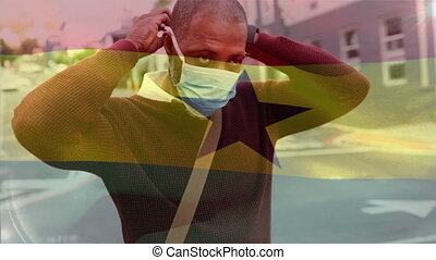 Animation of Ghana flag waving over mixed race man putting a face mask on. Covid-19 coronavirus national health safety concept digital composite