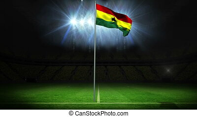 Ghana national flag waving on flagpole against football pitch with spotlights and flashes