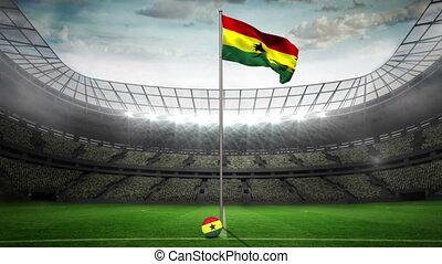Ghana national flag waving on flagpole in football stadium...