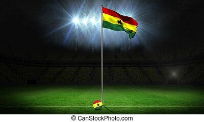 Ghana national flag waving on flagpole on football pitch...