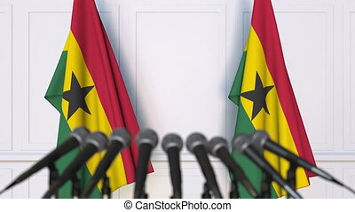 Ghanaian official press conference. Flags of Ghana and...