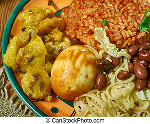Waakye, Ghanaian cuisine, cooked rice and beans, mixed with boiled eggs, stewed meat. Traditional assorted African dishes, Top view.