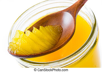 Ghee or clarified butter in jar and wooden spoon isolated on white background. Close up