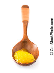 Ghee or clarified butter in wooden spoon isolated on white background.