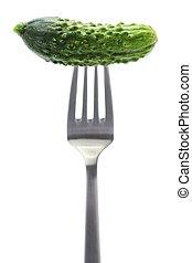 gherkin, garden fresh cucumber on fork, white background