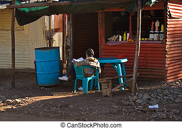 ghetto life - girl doing her homework at her mother shop,...
