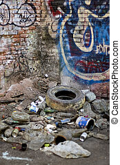 An abandoned area that is covered with trash and street graffiti. This makes an excellent background or backdrop. Shallow depth of field.