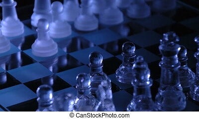 A close up shot of a glass chess board playing mysteriously playing itself.