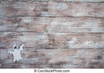 Ghost made of felt on a light wooden background. Place for your text