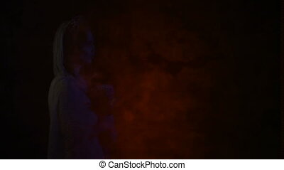 Ghost of a dead bride in white dress and wedding veil is appearing in the picture. Image of a young woman with skull mask on her face is flashing in the screen and moving from left to right side.
