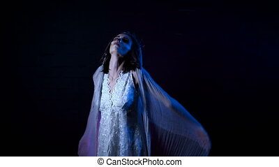 Ghost of young bride in white dress and veil. Moving scarry girl in with halloween make-up is standing against black background. Mysterious womanin horror behind .