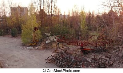 Rusty carousel in the amusement park of the city of Pripyat, Abandoned deserted city after a nuclear disaster. Views of the city of Pripyat near the Chernobyl nuclear power plant, aerial view.