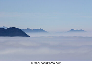 Mountain tops appear as ghostly shapes through thick fog.