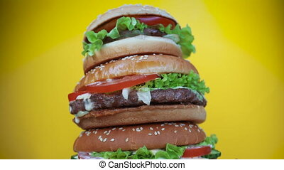 Giant delicious fresh burgers as cake rotating on yellow...