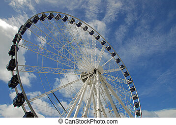 A giant ferris wheel against a deep blue sky with scattered cloud