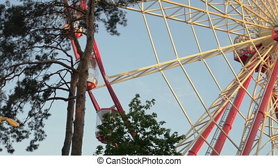 Giant ferris wheel against blue sky and white cloud which...