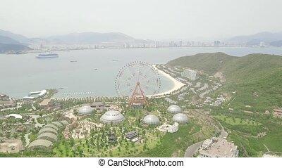 Giant ferris wheel in amusement park on sea and modern city landscape. Amusement park with large ferris wheel on sea, mountain and summer city background.