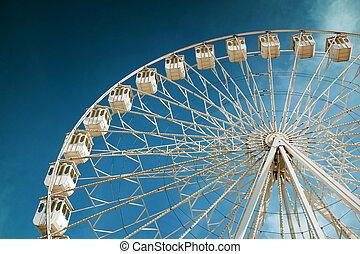 White ferris wheel in a fair and amusement park under blue sky