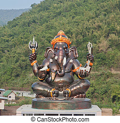 Giant Hindu God Ganesh on top of the building in a temple in...