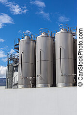 Giant industrial tanks on the bright blue sky