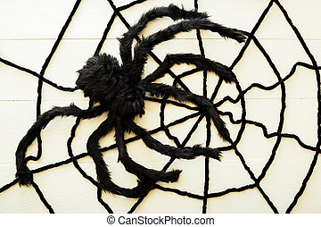 Giant spider on a web on a white wooden background. Halloween decorations concept. Flat lay, top view, copy space.