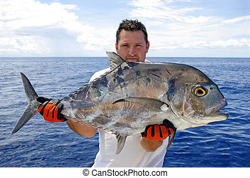 Deep sea fishing - Fisherman holding a trevally jack
