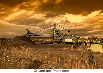 Giant wheel excavator in brown coal mine at sunset. Industrial landscape.