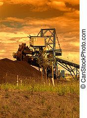 Giant wheel excavator in brown coal mine, sunset sky.