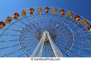 Giant colored wheel with its orange and yellow chairs by beautiful weather