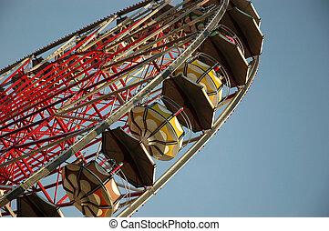 Giant farris wheel against blue sky background