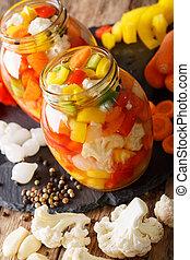 Giardiniera - vrelish of pickled vegetables in vinegar closeup. vertical