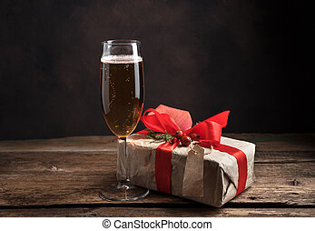 Gift and a glass of champagne on a wooden background.