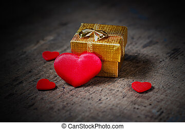 Gift and a lot of hearts on a wooden surface