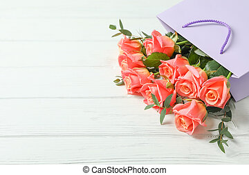 Gift bag with bouquet of pink roses on white background, space for text