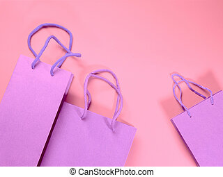 Gift bags on pink cardboard background - Festive gift bags ...