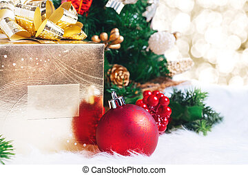gift box and ball decoration under christmas tree on white fer with gold bokeh light background