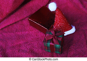 Gift box and christmas hat with macro close up on red carpet backgrounds