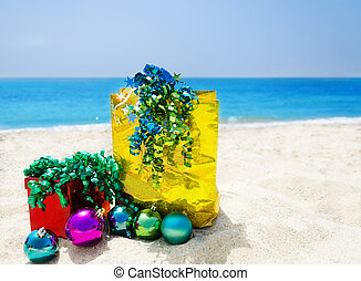 Gift box and gift bag on the beach - holiday concept
