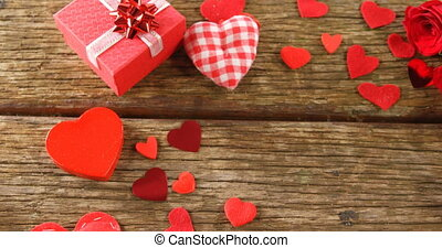 Gift box and heart shape confettis on wooden plank 4k - Gift...