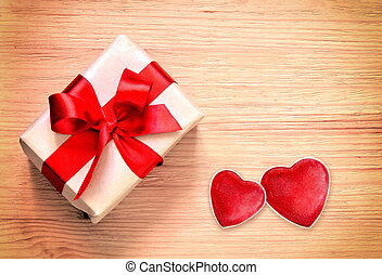 Gift box and hearts on wooden background.