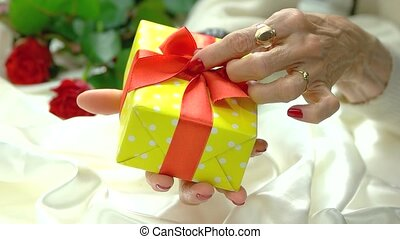 Gift box and manicured hand, slow motion. Elderly woman hand...