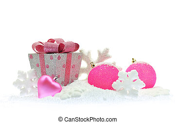 Gift box and pink Christmas ornaments on snow