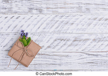 Gift box and posy of lavender on wooden background