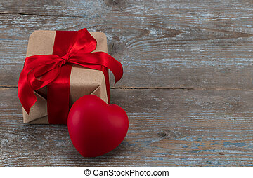 Gift box and red heart on the wooden background. Red ribbon. Valentine's Day gift