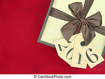 Gift box and tags with new year 2016 on red background