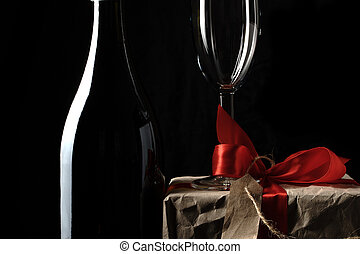 Gift box, champagne and glass on a dark background.